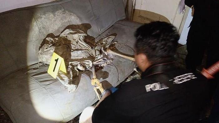 Polisi memeriksa kerangka manusia berposisi duduk di sofa rumah kosong. (Foto: dok. Polsek Margahayu)