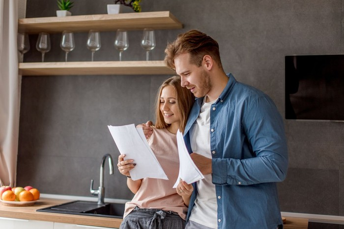 Confident couple trying to manage domestic finances, calculating and making notes