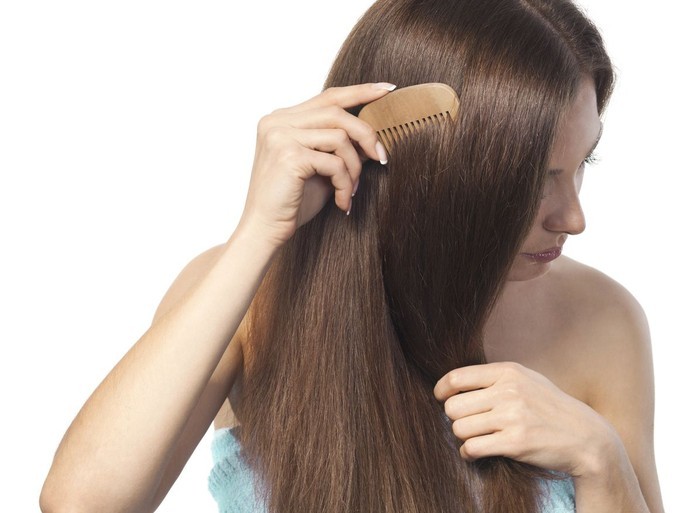 Young brunette lady combing her beautiful long hair. isolated white