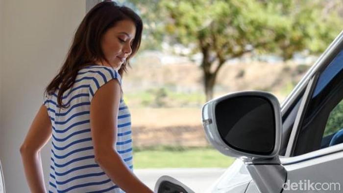 Pengendara wanita mengisi baterai mobil Chrysler Pacifica