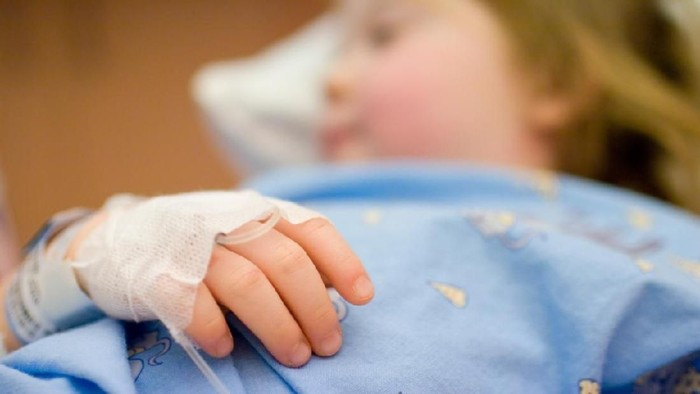 Close up of the hand of a little girl, lying in a hospital bed. Hand is tied down, with tube for an infusion. Focus on the hand.