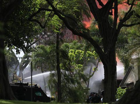 Petugas saat berupaya memadamkan kebakaran yang menyelimuti sebuah rumah yang menjadi lokasi penembakan di Hawaii