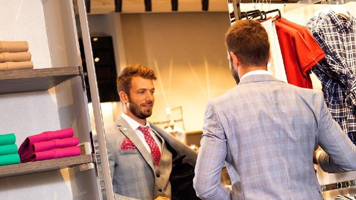 client is an elegant guy trying hat in a store by the mirror. In the background classic suits and jackets