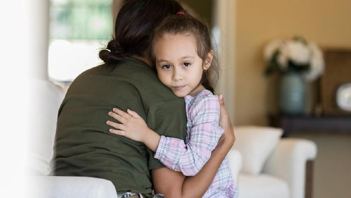 Little girl looks at the camera with a sad expression while hugging her military mom before she leaves for military deployment.