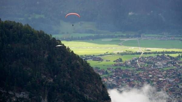 Gurskyberlibur di Interlaken, Swiss, bersama istrinya. ursky menggantung lebih dari dua menit di salah satu rangka gantole dan tubuh instrukturnya. Ia terbang tinggi di atas pepohonan dan berpegangan dengan satu tangan (Foto: Chris Gursky/CNN)