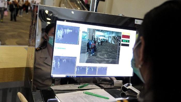 Petugas memantau suhu tubuh penumpang menggunakan alat pemindai suhu tubuh di Terminal Kedatangan Internasional Bandara Internasional I Gusti Ngurah Rai, Bali, Rabu (22/1/2020). Alat pemindai suhu tubuh tersebut dipasang Kantor Kesehatan Pelabuhan (KKP) Kelas I Denpasar sebagai upaya pengawasan dan antisipasi penyebaran Virus Corona yang mewabah dari Wuhan, China. ANTARA FOTO/Fikri Yusuf/hp.