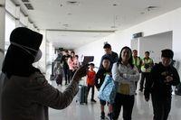 Petugas Bandara Juanda melakukan pemeriksaan suhu tubuh penumpang.