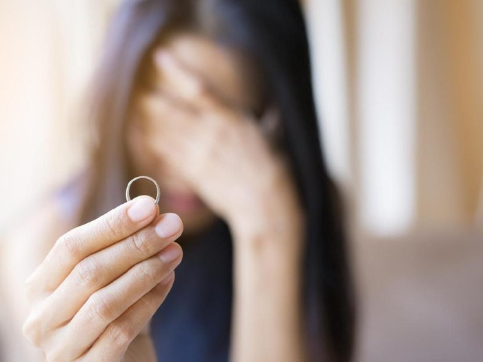 The woman holds the wedding ring and weeps.