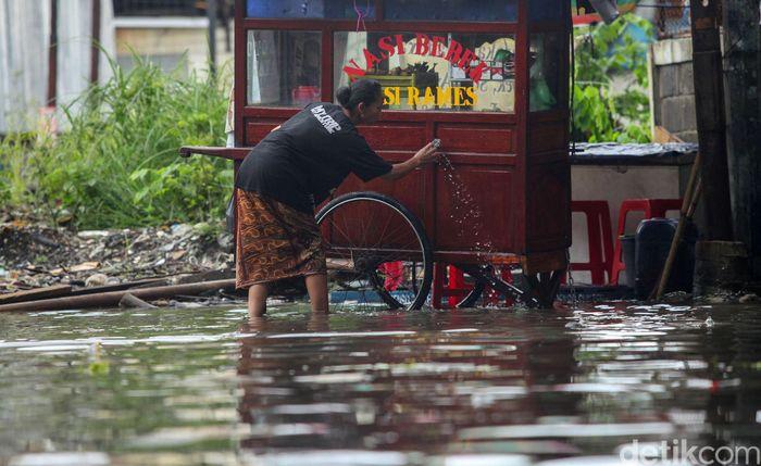 Seorang pedagang memanfaatkan air genangan banjir untuk membersihkan gerobak dagangannya di kawasan Sunter, Jakarta, Jumat (24/1/2020).