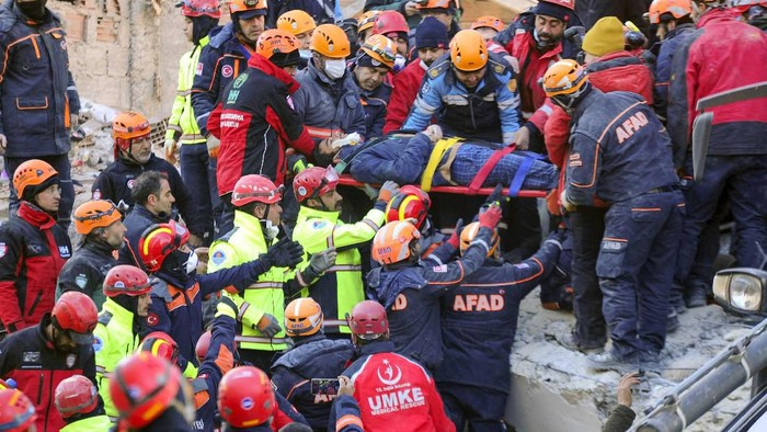Rescue workers carry a wounded woman after they rescued her from the debris of a collapsed building following a strong earthquake in Elazig in the eastern Turkey, Saturday, Jan. 25, 2020. The earthquake rocked eastern Turkey on Friday, causing some buildings to collapse and killing scores of people, Turkish officials said. (IHA via AP)