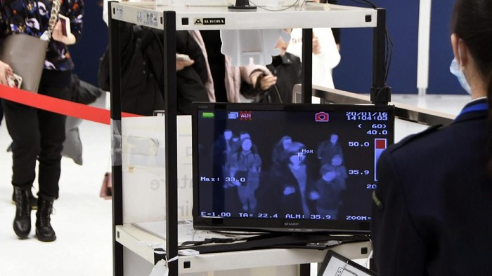 Airport personnel look at thermal scanners as they check on arriving passengers at Manilas international airport, Philippines, Thursday, Jan. 23, 2020. The government is closely monitoring arrival of passengers as a new coronavirus outbreak in Wuhan, China has infected hundreds and caused deaths in that area. (AP Photo/Aaron Favila)