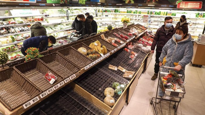 Shoppers wearing face masks look for groceries with many empty shelves at a supermarket in Wuhan in central Chinas Hubei province, Saturday, Jan. 25, 2020. The virus-hit Chinese city of Wuhan, already on lockdown, banned most vehicle use downtown and Hong Kong said it would close schools for two weeks as authorities scrambled Saturday to stop the spread of an illness that is known to have infected more than 1,200 people and killed 41, according to officials. (Chinatopix via AP)