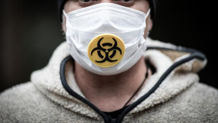 Man wearing a surgical mask with a biohazard logo close up.