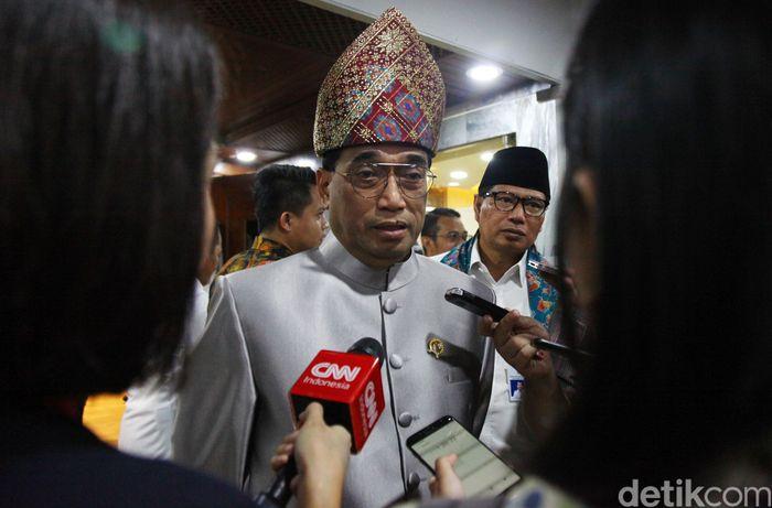 Menteri Perhubungan (Menhub) Budi Karya Sumadi mengenakan pakaian adat saat mengikuti rapat evaluasi mudik Natal 2019 dan Tahun Baru 2020 (Nataru) bersama Komisi V DPR RI, Jakarta, Selasa (28/1/2020).