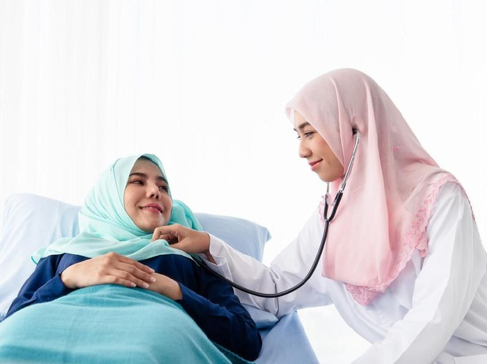 A young beautiful Muslim doctor is using a stethoscope to listen to the patients heartbeat at the bed in the hospital examination room.