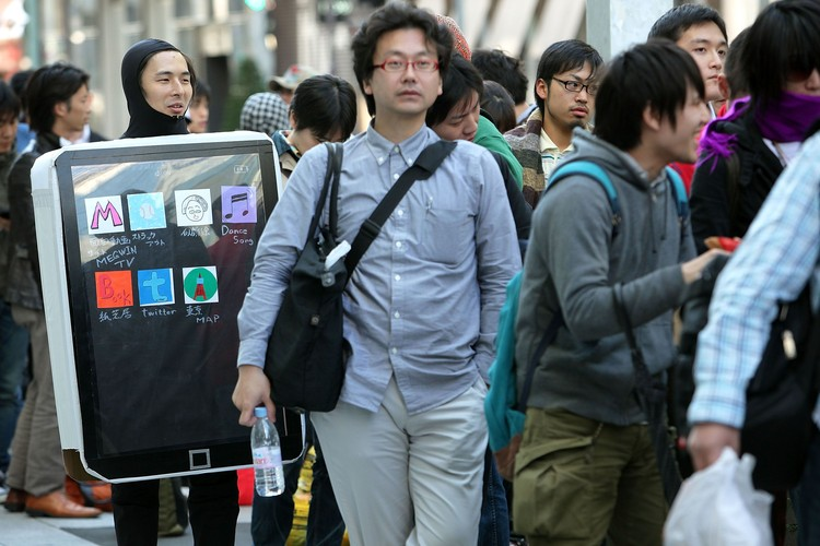 TOKYO - MAY 28:  Ken Sekine (L) in an iPad costume waits in a queue for Apple Inc.s iPad tablet computers outside the Apple Store Ginza on the day of its Japanese launch on May 28, 2010 in Tokyo, Japan. The iPad, which has already sold over 1 million units in the U.S. since its release, is available in both the Wi-Fi and the Wi-Fi + 3G models in Australia, Canada, France, Germany, Italy, Japan, Spain, Switzerland and the UK with its international launches.  (Photo by Kiyoshi Ota/Getty Images)