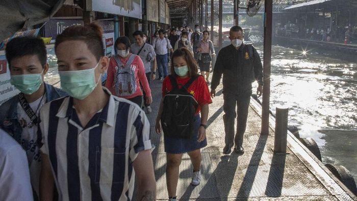 Boat passengers on a jetty wear face masks in Bangkok, Thailand, Tuesday, Jan. 28, 2020, to protect themselves from the coronavirus. Panic and pollution drive the market for protective face masks in Asia, where fear of the virus from China is straining supplies and helping make mask-wearing the new normal. Thailands Public Health ministry said Tuesday six more people have tested positive with the new virus infection, raising to 14 the total number of cases in the country. (AP Photo/Gemunu Amarasinghe)