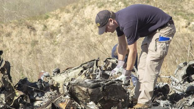 In this image taken Monday, Jan. 27, 2020, and provided by the National Transportation Safety Board, NTSB investigators Adam Huray, foreground, and Carol Hogan examine wreckage as part of the NTSB's investigation of a helicopter crash near Calabasas, Calif. The Sunday, Jan. 26 crash killed former NBA basketball player Kobe Bryant, his 13-year-old daughter, Gianna, and seven others (James Anderson/National Transportation Safety Board via AP)
