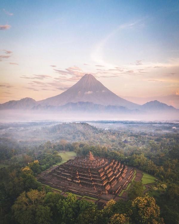 Candi Borobudur tengah jadi perbincangan karena unggahan dari Instagram Kemenparekraf. Postingan tersebut memperlihatkan foto Borobudur dengan latar sebuah gunung yang lancip. (Instagram/indtravel)