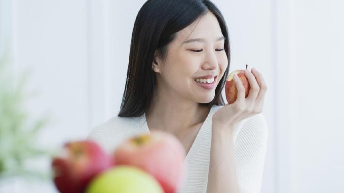 healthy beautiful attractive long black hair woman happiness smile hand hold red apple with foreground of fruit bowl white room interior background