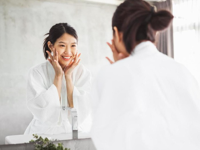 Asian woman cleaning face front of mirror, skin care and cosmetic removal concept
