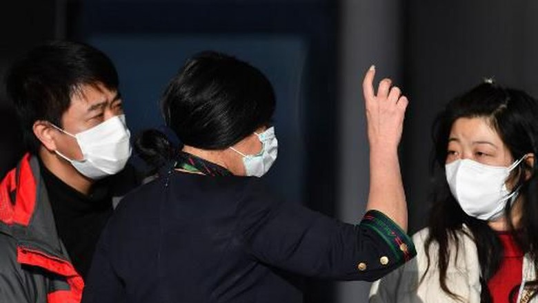 A company employee (C) assists passengers waiting to check in by the counter of China Southern Airlines at Romes Fiumicino airport for a flight returning to Wuhan, China, after it landed early on January 23, 2020. - China banned trains and planes from leaving a major city at the centre of a virus outbreak on January 23, seeking to seal off its 11 million people to contain the contagious disease that has claimed 17 lives, infected hundreds and spread to other countries. (Photo by Tiziana FABI / AFP)