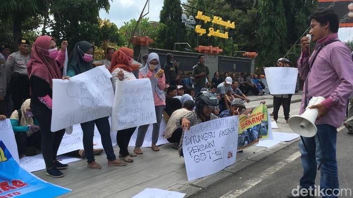 Puluhan warga demo di depan kantor DPRD dan Pemkot Mojokerto. Massa protes soal 8 proyek drainase dan saluran air yang tidak tuntas.