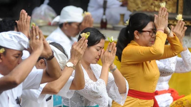 Pemuka agama Hindu memercikkan air suci saat persembahyangan bersama di Pura Luhur Candi Narmada Tanah Kilap, Denpasar, Bali, Jumat (31/1/2020). Persembahyangan yang dilakukan Dinas Pariwisata Provinsi Bali dan diikuti sejumlah pelaku industri pariwisata tersebut diselenggarakan untuk mendoakan keselamatan dunia dan memohon agar Bali dijauhkan dari penyebaran virus Corona. ANTARA FOTO/Fikri Yusuf/nz