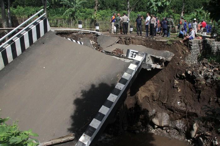 Seorang warga melihat jembatan yang ambrol di Dau, Malang, Jawa Timur, Jumat (31/1/2020). Naiknya volume air sungai akibat tingginya intensitas hujan di kawasan tersebut dalam dua hari terakhir membuat jembatan penghubung antar desa tersebut ambrol. ANTARA FOTO/Ari Bowo Sucipto/foc.