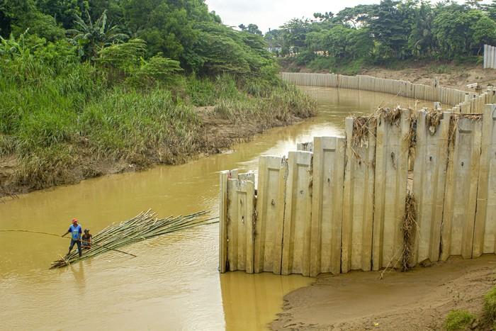 Warga menggunakan perahu rakit saat melintasi sungai Cibeet yang terpasang dinding turap (sheet pile) di Karawang, Jawa Barat, Jumat (31/1/2020). Balai Besar Wilayah Sungai (BBWS) Citarum menyatakan pemasangan dinding turap di tengah sungai Cibeet oleh oknum pengusaha Kabupaten Bekasi tersebut tidak memiliki izin dan dapat mempersempit bentuk sungai serta menyebabkan banjir. ANTARA FOTO/M Ibnu Chazar/nz.