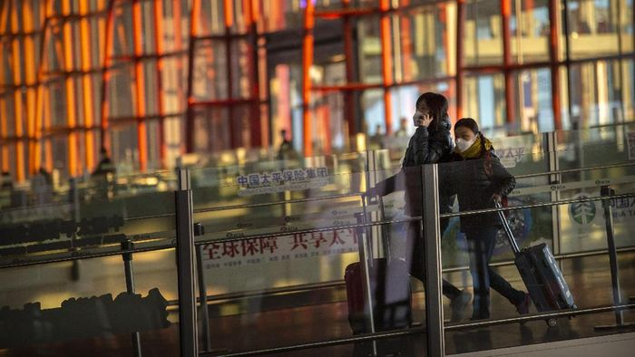 Travelers wearing face masks walk along a concourse at Beijing Capital International Airport in Beijing, Thursday, Jan. 30, 2020. China counted 170 deaths from a new virus Thursday and more countries reported infections, including some spread locally, as foreign evacuees from Chinas worst-hit region returned home to medical observation and even isolation. (AP Photo/Mark Schiefelbein)