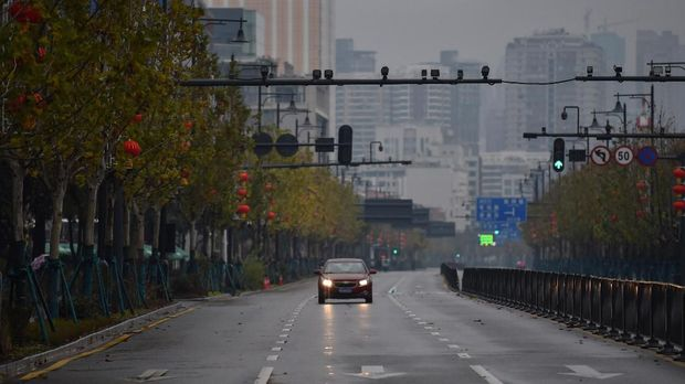 A lone car drives down a disserted street in Wuhan on January 26, 2020, a city at the epicentre of a viral outbreak that has killed at least 56 people and infected nearly 2,000. - China on January 26 expanded drastic travel restrictions to contain the viral contagion, as the United States and France prepared to evacuate their citizens from the quarantined city at the outbreak's epicentre. (Photo by Hector RETAMAL / AFP)