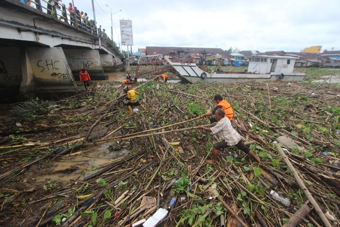 Sampah membuat transportasi air di sungai yang berada di kawasan Kalimantan Selatan terganggu. Petugas dan warga pun membersihkan sampah-sampah itu.