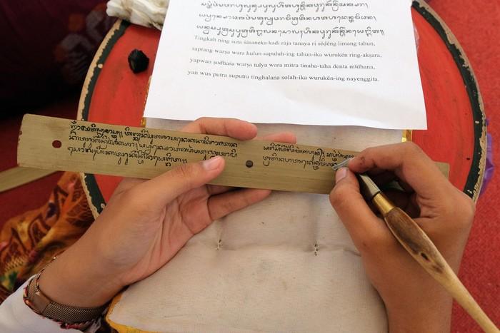 Peserta menuliskan aksara Bali di atas daun lontar dalam festival