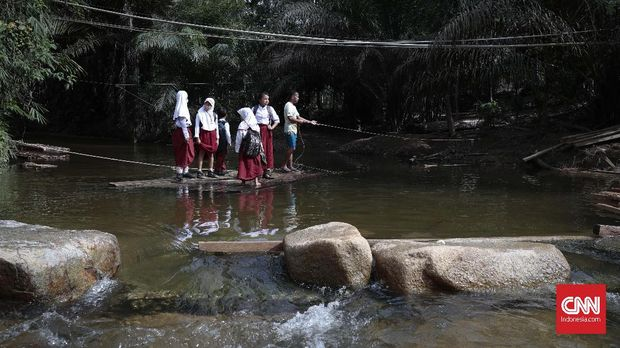 Murid-murid pulang mengunakan rakit usai belajar di SDN 10/Sekolah Marjinal yang terletak di Dusun Sialang Harapan Desa Batu Sasak, Kecamatan Kampar Kampar Kiri, Kabupaten Kampa