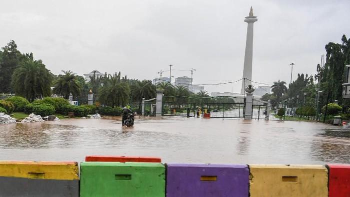 Warga mendorong motor melintasi banjir di kawasan Monas, Jalan Medan Merdeka Barat, Jakarta, Minggu (2/2/2020). Hujan deras yang mengguyur Jakarta pada Minggu (2/2) pagi menyebabkan beberapa ruas jalan di ibu kota tergenang banjir dengan ketinggian 10-50 centimeter. ANTARA FOTO/Hafidz Mubarak A/aww.