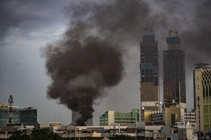 Kepulan asap hitam membumbung tinggi dari atas bangunan kompleks ruko tekstil yang terbakar di kawasan Tanah Abang, Jakarta, Senin (3/2/2020). Kurang lebih 12 unit mobil pemadam kebakaran dikerahkan untuk memadamkan api, sedangkan penyebab kebakaran masih dalam penyelidikan pihak yang berwenang. ANTARA FOTO/Aprillio Akbar/ama.