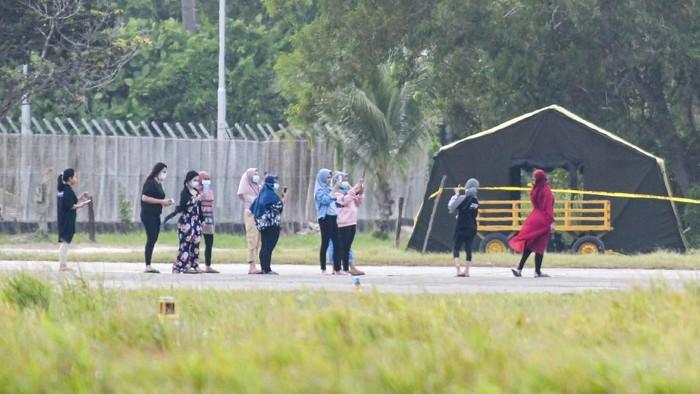 Sejumlah Warga Negara Indonesia (WNI) asal Wuhan, Hubei, China beraktivitas di depan Hanggar Pangkalan Udara Raden Sadjad, Ranai, Natuna, Kepulauan Riau, Selasa (4/2/2020). Menurut data Kementerian Kesehatan bahwa 238 orang WNI yang menjalani proses observasi sebagai antisipasi tertular virus Corona bahwa kesehatannya dalam keadaan baik dan sehat, tidak ada satupun dari mereka yang menunjukkan gejala infeksi seperti demam, batuk dan pilek. ANTARA FOTO/M Risyal Hidayat/hp.