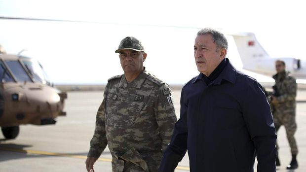 Turkey's National Defence Minister Hulusi Akar, right, arrives to inspect troops at the border with Syria, in Hatay, Turkey, Monday, Feb. 3, 2020. Turkey hit targets in northern Syria, responding to shelling by Syrian government forces that killed at least eight Turkish military personnel, Turkish President Recep Tayyip Erdogan said Monday. A Syrian war monitor said 13 Syrian troops were also killed.(Turkish Defence Ministry via AP, Pool)