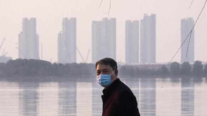 FILE - In this Jan. 30, 2020 file photo, a man wears a face mask as he stands along the waterfront in Wuhan in central Chinas Hubei Province. Arek and Jenina Rataj were starting a new life in the Chinese industrial center of Wuhan when a viral outbreak spread across the city of 11 million. While they were relatively safe sheltering at home, Arek felt compelled to go out and document the outbreak of the new type of coronavirus. Among his subjects: the construction of a new hospital built in a handful of days; biosecurity check points; and empty streets.(AP Photo/Arek Rataj, File)