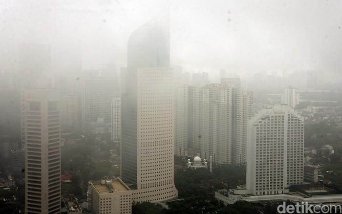 Hujan yang mengguyur wilayah Jakarta membuat gedung pencakar langit di ibu kota tertutup kabut. Berikut potretnya.
