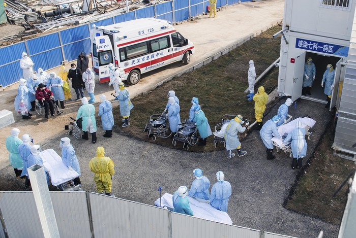 In this photo released by Chinas Xinhua News Agency, medical workers in protective suits help transfer the first group of patients into the newly-completed Huoshenshan temporary field hospital in Wuhan in central Chinas Hubei province. China said Tuesday the number of infections from a new virus surpassed 20,000 as medical workers and patients arrived at a new hospital and President Xi Jinping said