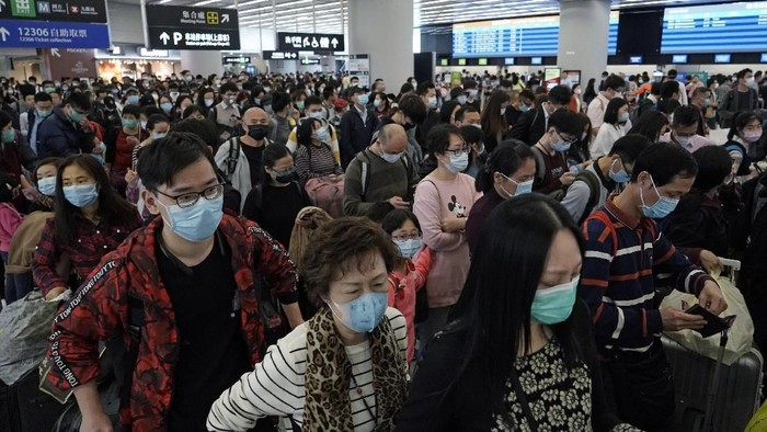 FILE - In this Thursday, Jan. 23, 2020 file photo, Passengers wear protective face masks at the departure hall of the high speed train station in Hong Kong.  Fear about the effects of a new virus found in China is spreading faster through financial markets around the world than the sickness itself. U.S. stocks fell to their biggest weekly loss since early October on worries that the new coronavirus could ultimately hurt travel and global economic growth. (AP Photo/Kin Cheung, File)