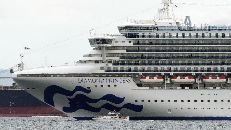A small boat navigates near a cruise ship Diamond Princess anchoring off the Yokohama Port Tuesday, Feb. 4, 2020, in Yokohama, near Tokyo. Japanese health officials are conducting extensive medical checks on all 3,700 passengers and crew of the cruise ship that returned to the country after one passenger tested positive for the new coronavirus. (AP Photo/Eugene Hoshiko)