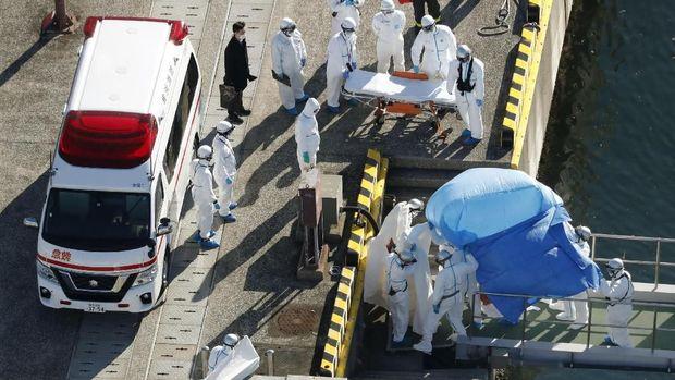 Petugas medis saat mengevakuasi penumpang yang positif virus corona dari sebuah kapal pesiar di Yokohama