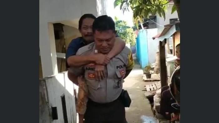 Aiptu Ariffudin menggendong warga disabilitas di Palopo Sulsel