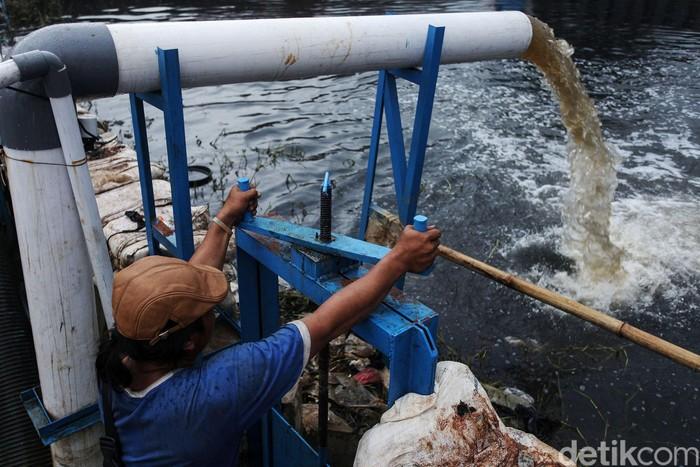 Seorang petugas tengah mengoperasikan mesin pompa di Kali Ledug, Periuk, Tangerang, Kamis (6/1/2020). Banjir yang melanda kawasan ini sejak 5 hari lalu membuat petugas siaga 24 jam.