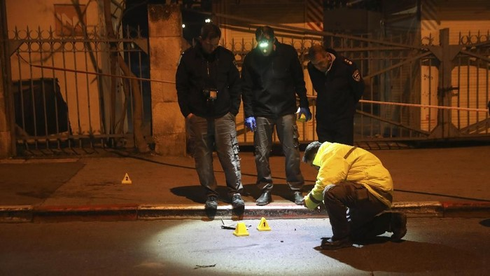 Israeli police officers inspect the scene of an attack in Jerusalem, early Thursday, Feb. 6, 2020. A Palestinian motorist slammed his car into a group of soldiers early on Thursday, wounding more than a dozen before fleeing the scene, Israeli police said. (AP Photo/Mahmoud Illean)