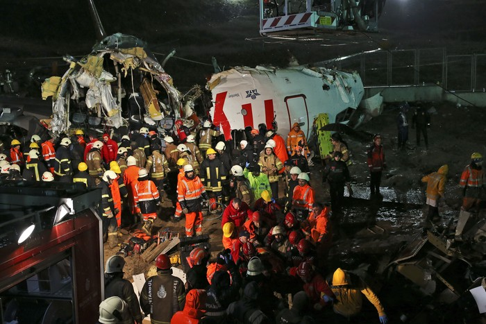 Rescue members and firefighters work around the wreckage of a plane after it skidded off the runway at Istanbul's Sabiha Gokcen Airport, in Istanbul, Wednesday, Feb. 5, 2020. The plane skidded off as it tried to land in bad weather, crashing into a field and breaking into pieces. Passengers had to evacuate through cracks in the smashed plane and authorities said 120 people were sent to the hospital with injuries. (AP Photo/Emrah Gurel)