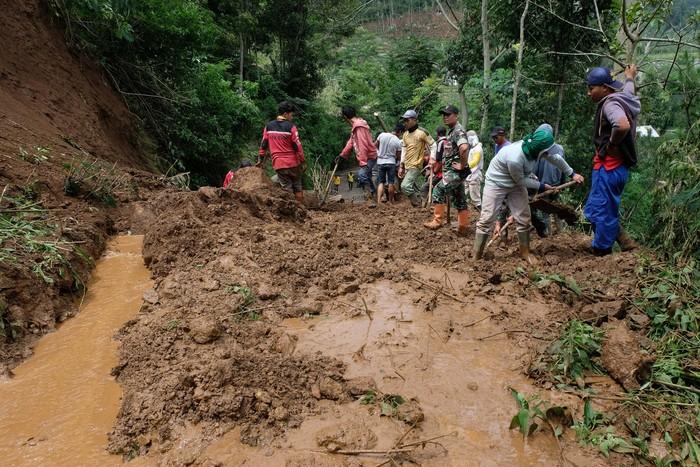 Sejumlah warga dibantu relawan dan anggota TNI menyingkirkan timbunan tanah longsor yang menutup jalan raya di kawasan lereng Gunung Prau, Desa Tawangsari, Wonoboyo, Temanggung, Jawa Tengah, Kamis (6/2/2020). Akibat curah hujan tinggi menyebabkan longsor di enam titik di jalur alternatif menuju dataran tinggi Dieng sehingga jalur tersebut ditutup total. ANTARA FOTO/Anis Efizudin/wsj.